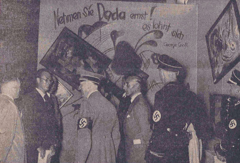 """Adolf Hitler and other Nazi officials take in the Dada wall at the """"Entartete Kunst"""" (""""Degenerate Art"""") exhibition in Munich on July 16, 1937. Originally published in the Nationalist Observer, South German issue, No. 199, July 18, 1937."""