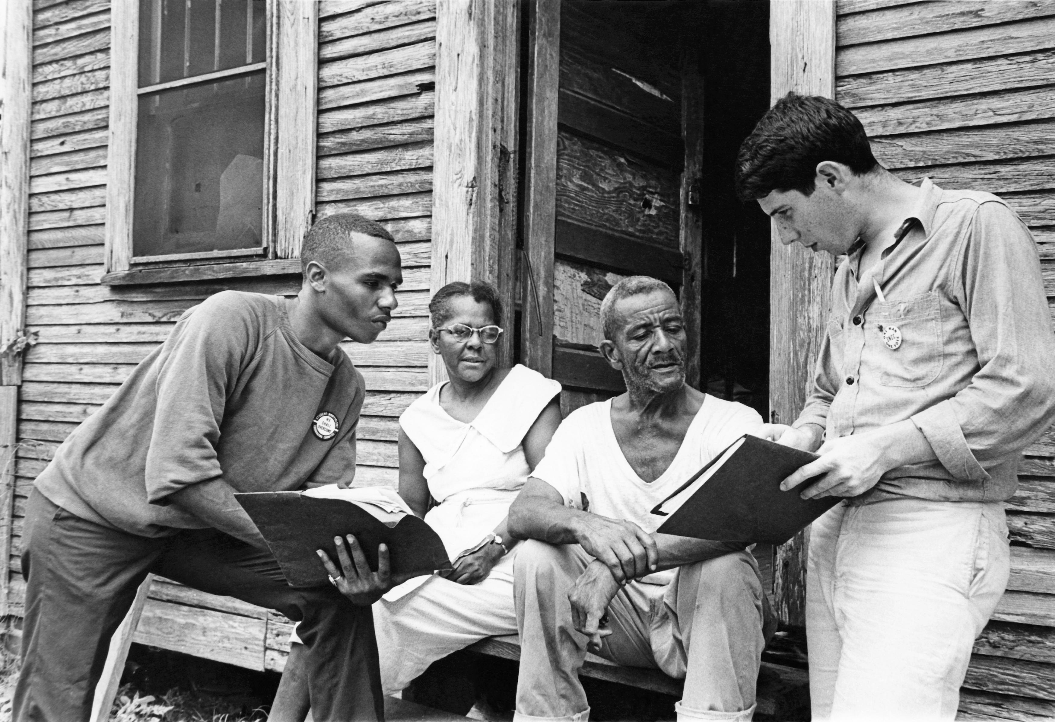 Johnny Waters, COFO block captain, Ceola Wallace and Jake Plum explains registration procedures to prospective voter Willie McGee in Hattiesburg, MS, 1964