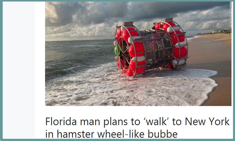 Man standing on surf inside of hamster-wheel like flotation device