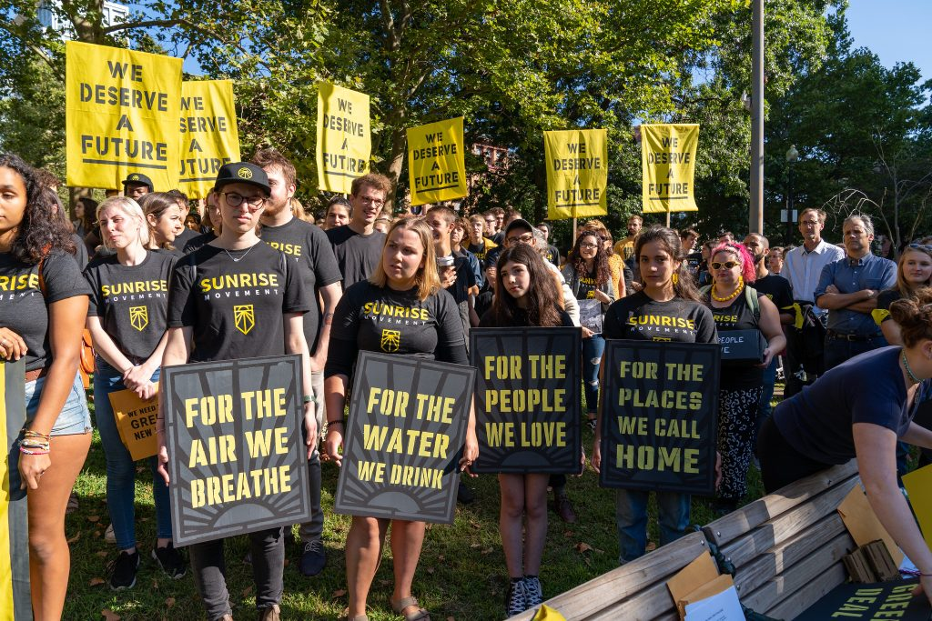 """Sunrise demonstrators protest. Their signs say """"for the air we breathe, for the water we drink, for the people we love, for the places we call home, we deserve a future."""""""
